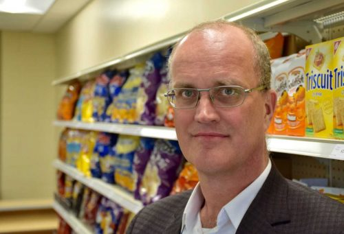 Prof. Mike von Massow standing in front of a grocery store shelf