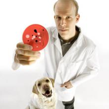 Prof. Scott Weese holding up a petri dish with a dog next to him