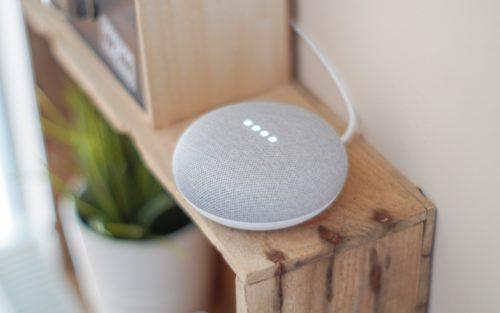 A Google Home speaker sits on a shelf