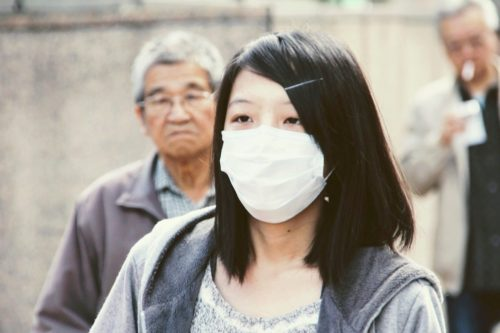 A woman wears a surgical mask
