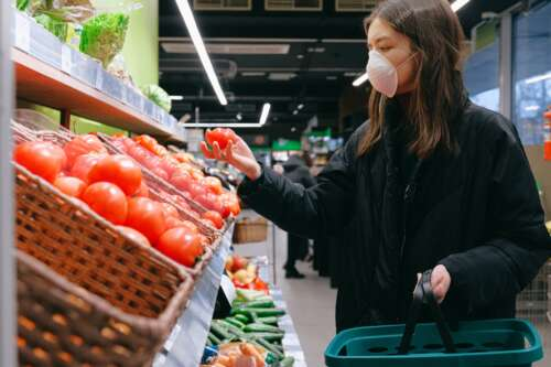 A woman wearing a face mask checks tomatoes in a grocery aisle