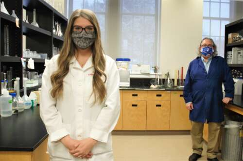 Two people stand in a lab, woman in front, man behind