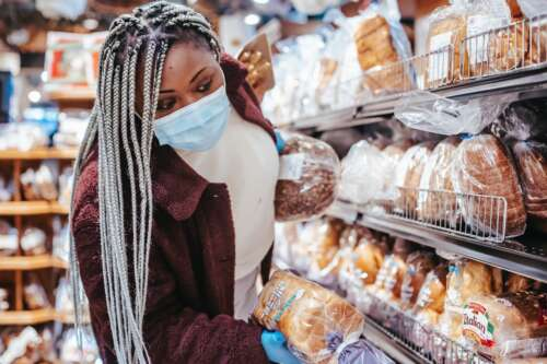 A woman wearing a mask shops for packaged bread