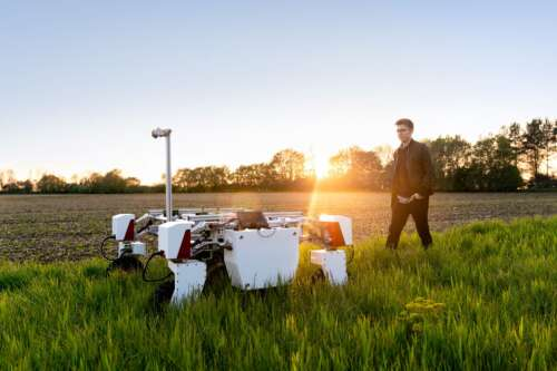 Male mechanical engineer with agricultural robot in field