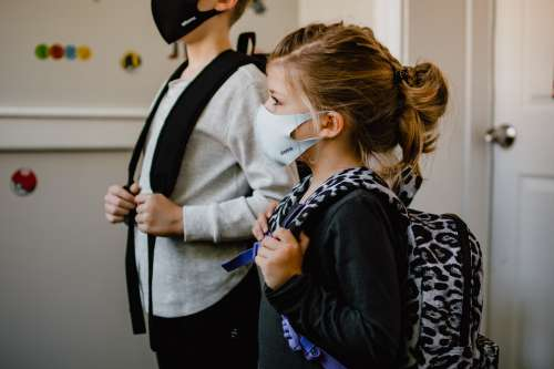 two schoolchildren wear masks and backpacks
